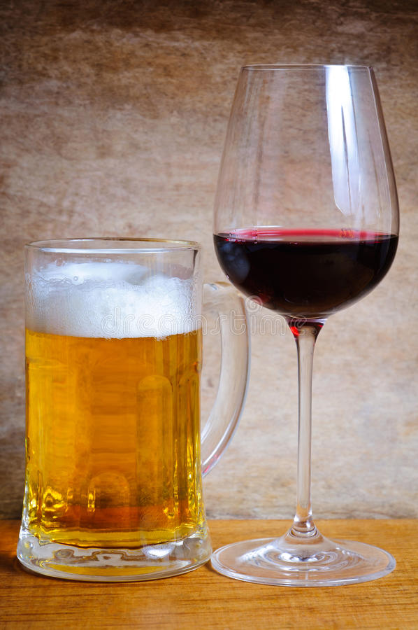 Beer mug and wine glass. On a wooden background stock images