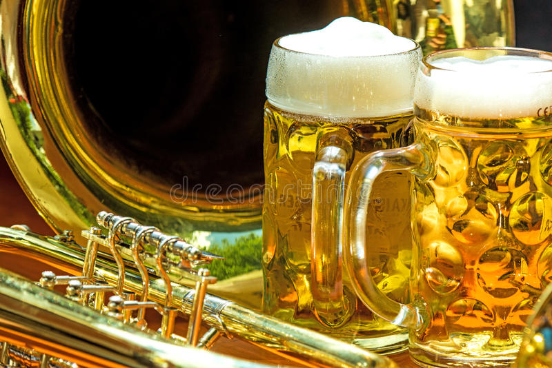 Beer mugs with trumpet. On a beer desk on a street party stock images