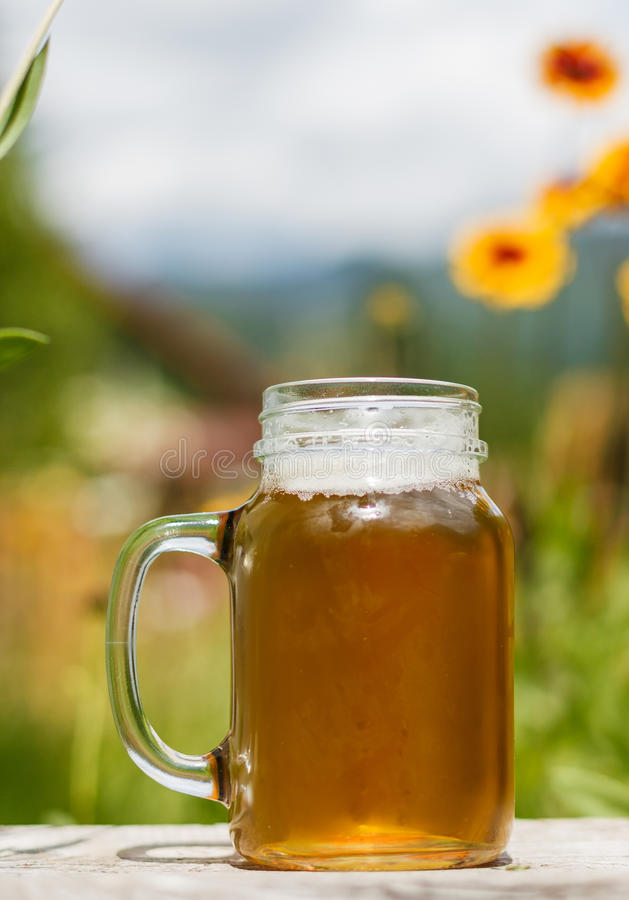 Beer and nature. Fresh cold beer mug outdoors, in the middle of the nature, under summer sunlight, surrounded by flowers and trees stock photo