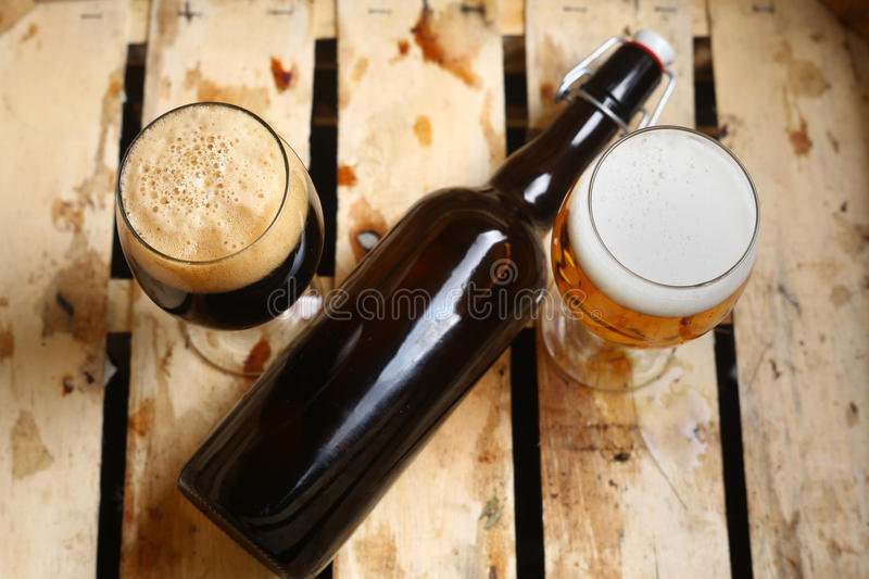 Beer percent. Bottle and full glasses of beer looking as a percent sign in a dirty wooden crate stock image