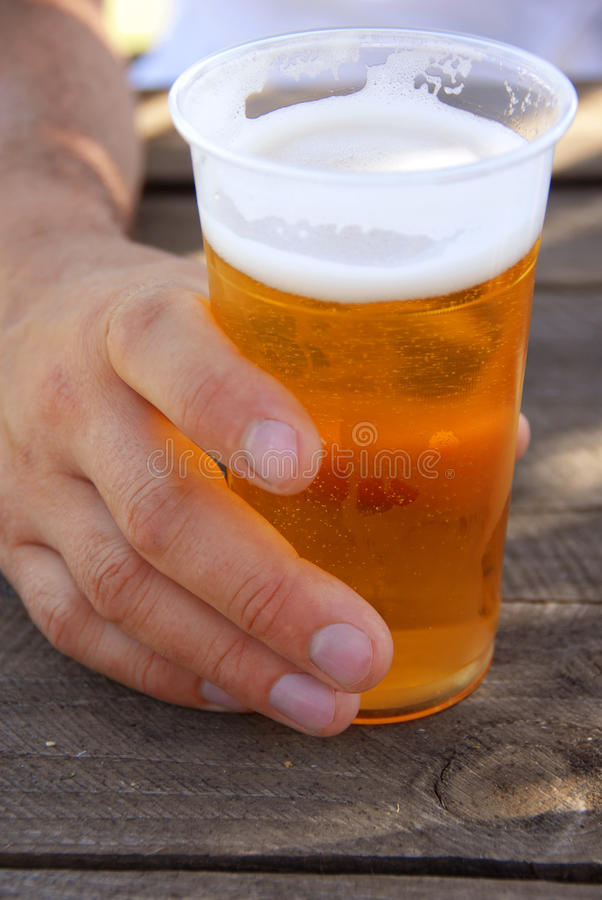 Beer in plastic glass. Orange beer in transparent plastic glass in man hand closeup outdoor royalty free stock image