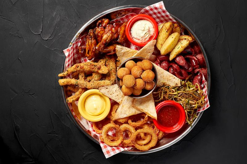 The beer plate with spicy chicken wings, calamari rings, fries onion rings, cheese balls, breaded, tartar sauce and stock images