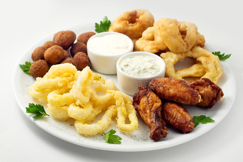 The beer plate with spicy chicken wings, calamari rings, fries onion rings, cheese balls, breaded, tartar sauce and garlic royalty free stock image