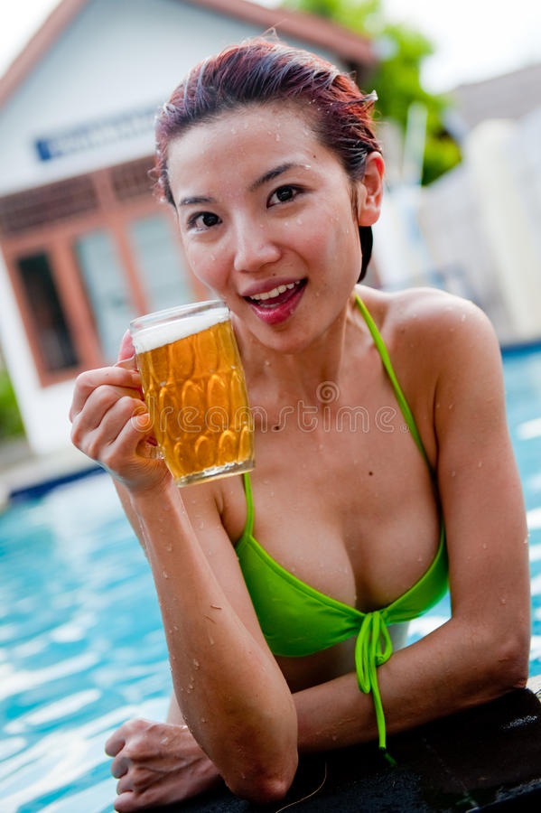 Beer In Pool. A young attractive Chinese woman drinking a beer in the pool royalty free stock photos