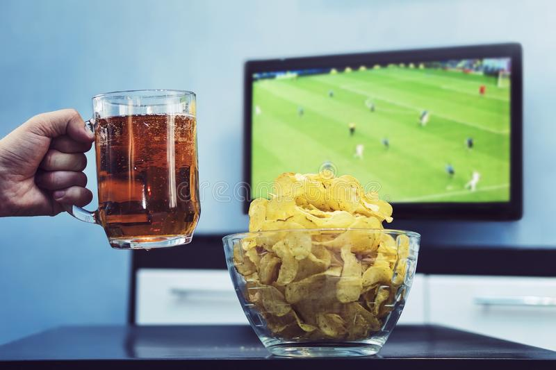 Beer potato chips and Sport on TV, A man raises a mug of dark beer celebrate the victory of his favorite team in the world Cup, stock photography