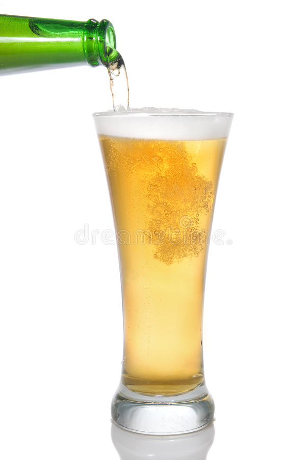 Beer pouring from bottle into glass. Isolated on white stock images