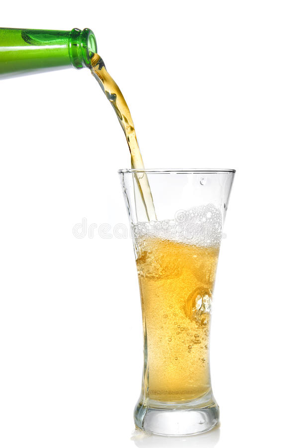 Beer pouring from bottle into glass. Isolated on white royalty free stock images