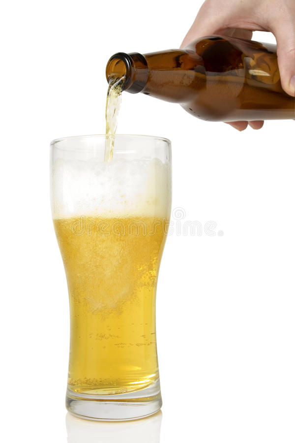 Beer pouring from bottle into glass stock photography