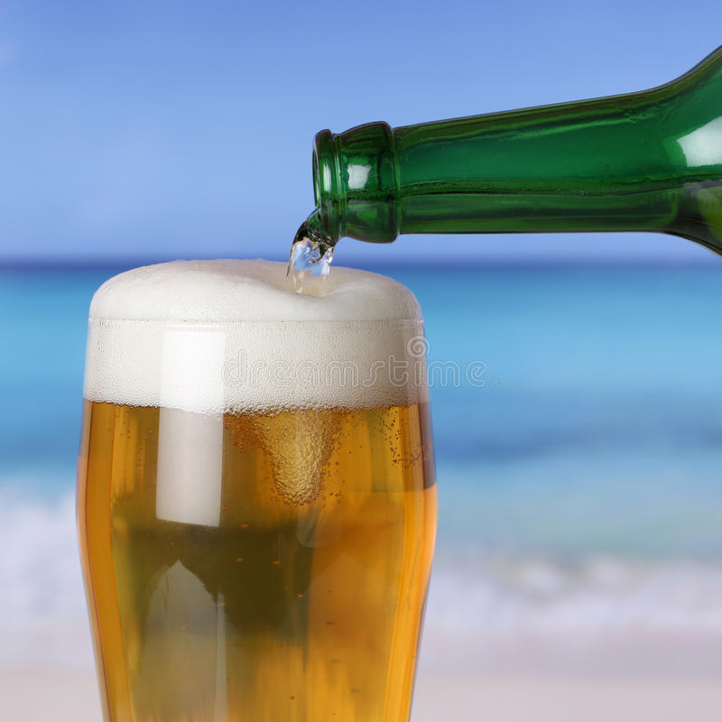 Beer pouring from bottle into glass on beach and sea. Beer pouring from a bottle into a glass on the beach and the sea royalty free stock photography