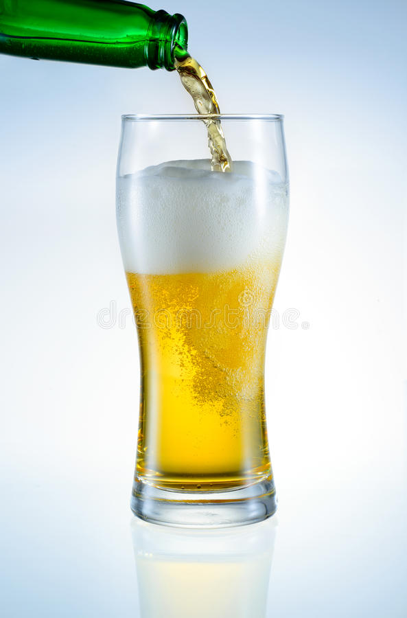 Beer is pouring from bottle into the glass. Isolated royalty free stock photo