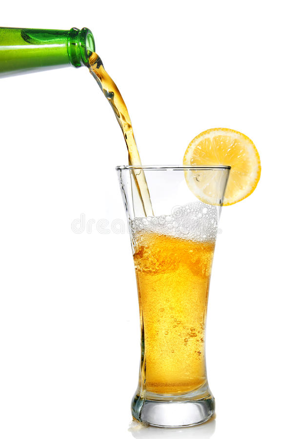 Beer pouring from bottle into glass. With lemon isolated on white royalty free stock photo