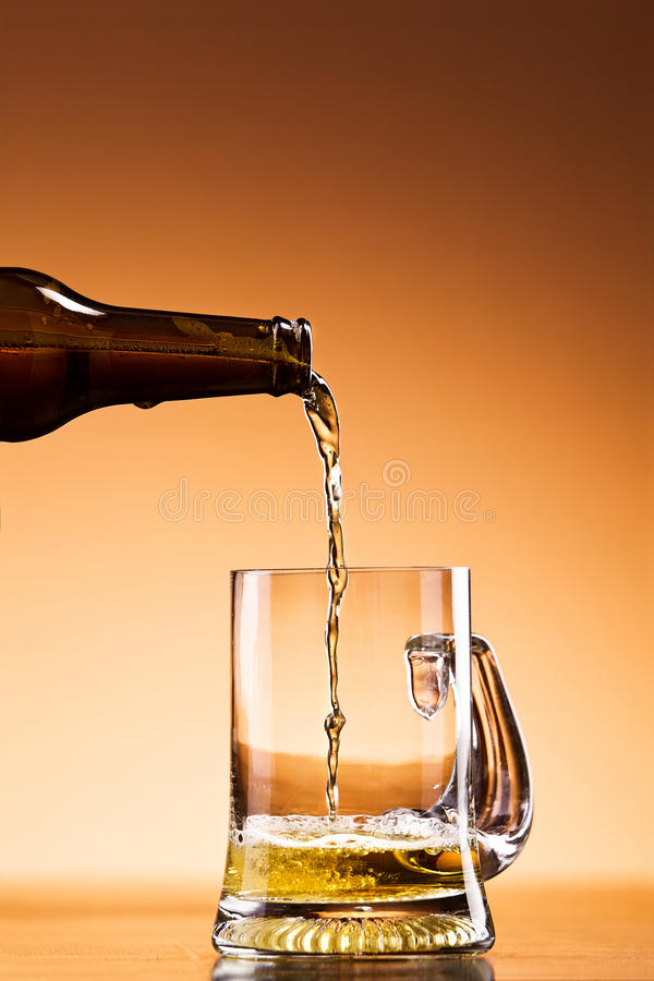 Beer pouring. Bottle of Beer pouring into a Glass Mug royalty free stock image
