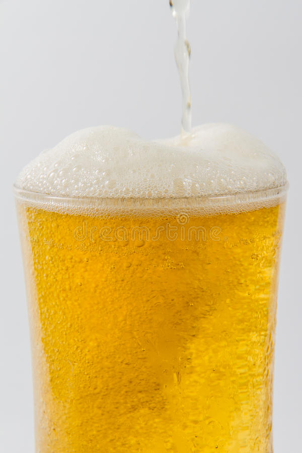 Beer. Pouring from bottle into glass on white royalty free stock photo