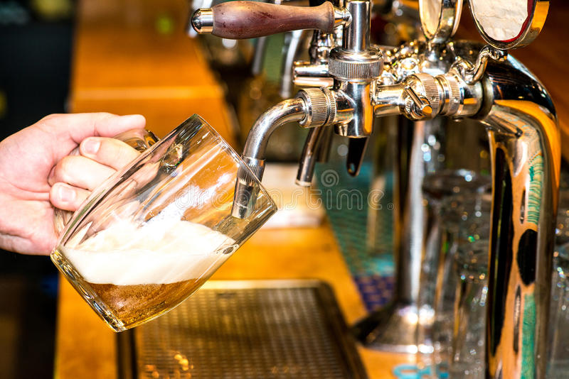 Beer pouring. Close-up of bartender hand at beer tap pouring a draught lager beer royalty free stock photography