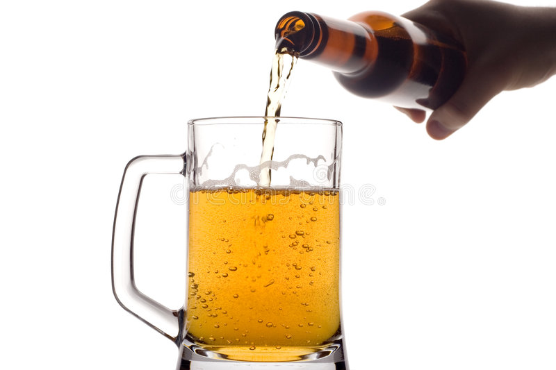 Beer pouring down from a bottle. Against white background stock image