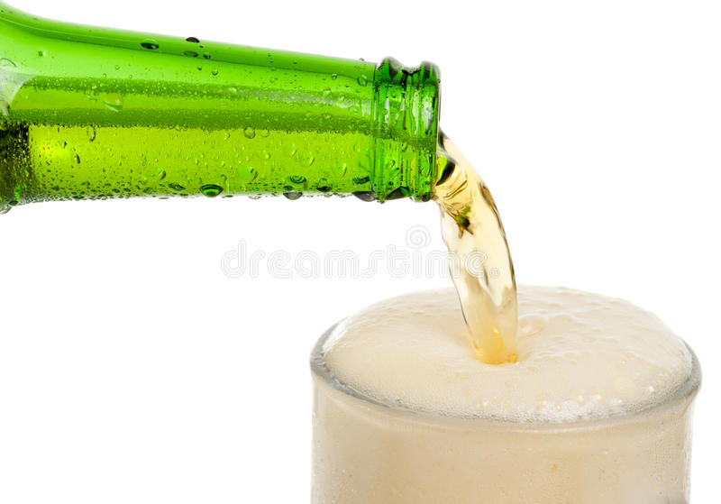Beer pouring in glass. Cool beer pouring in glass, lots of froth royalty free stock photos