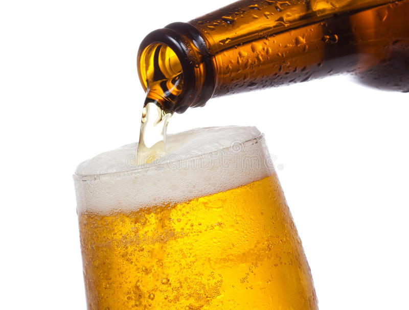Beer pouring into glass. On white background royalty free stock photos