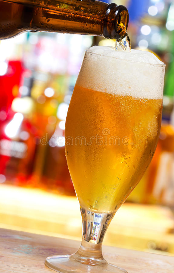 Beer pouring into glass. In a bar stock images