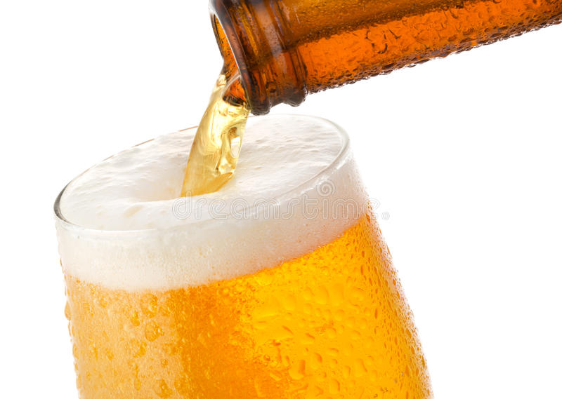 Beer pouring into glass. On white background stock image