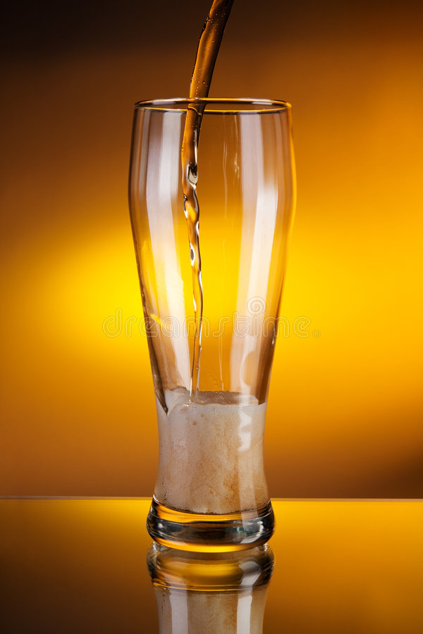 Beer pouring into a glass. In yellow lightning stock images