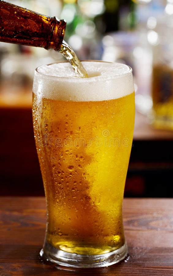 Beer pouring into glass. In a bar stock photo