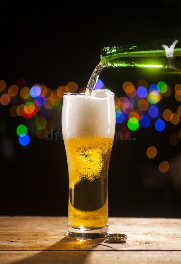 Beer is pouring into glass on bar lights background. Beer is pouring into glass on wooden table and bar lights background stock photography