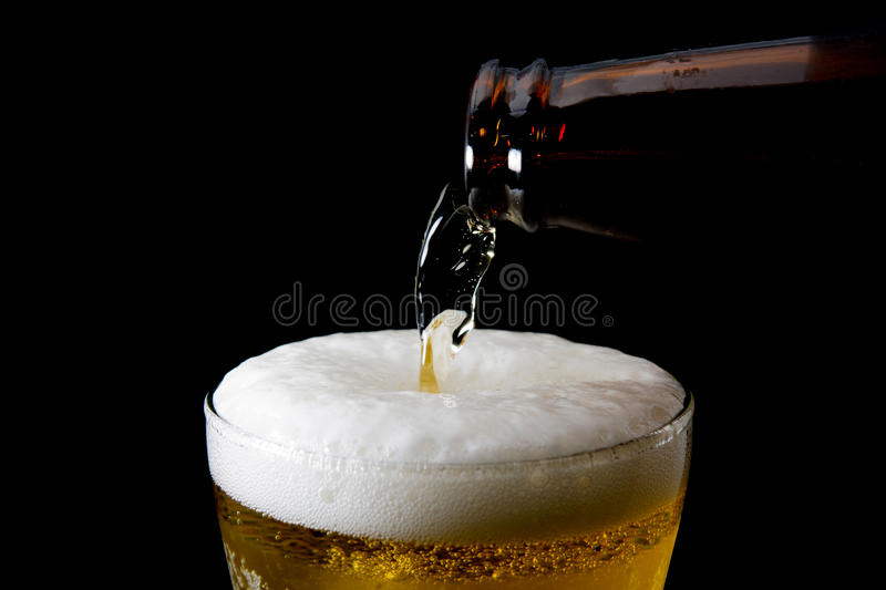 Beer is pouring into glass on black. Background royalty free stock photo