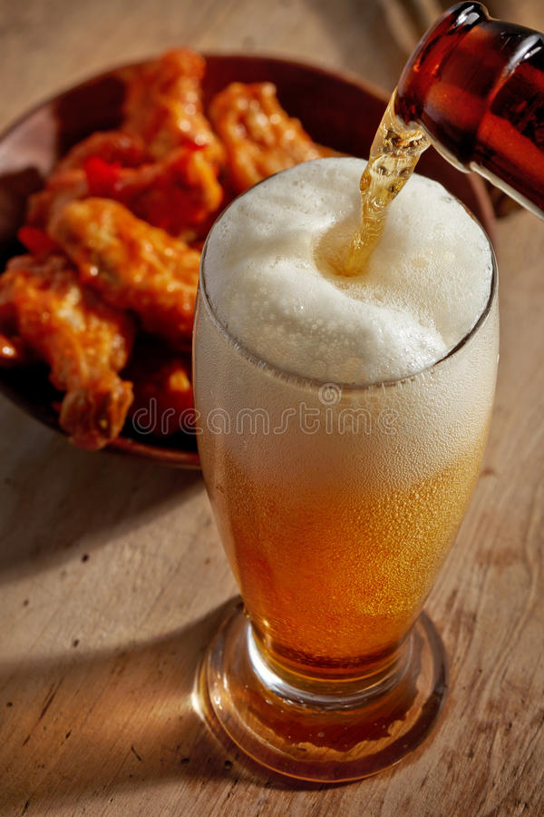 Beer pouring into glass. And fried chicken wings on wooden table royalty free stock photo