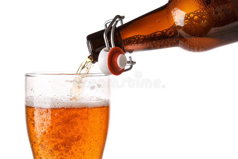 Beer is pouring into a glass. Over white background royalty free stock photography
