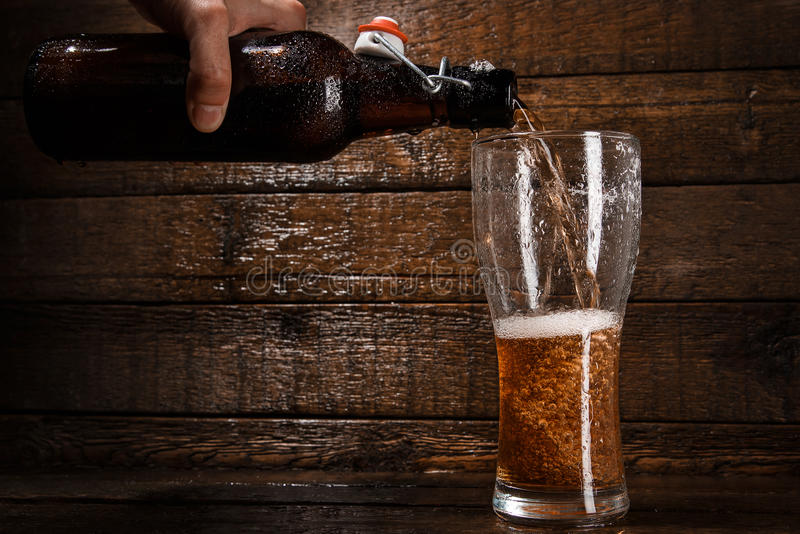 Beer is pouring into a glass. Over wooden background royalty free stock images