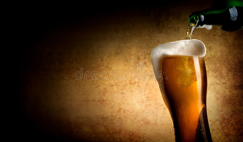 Beer pouring into glass. On a textured background royalty free stock photo