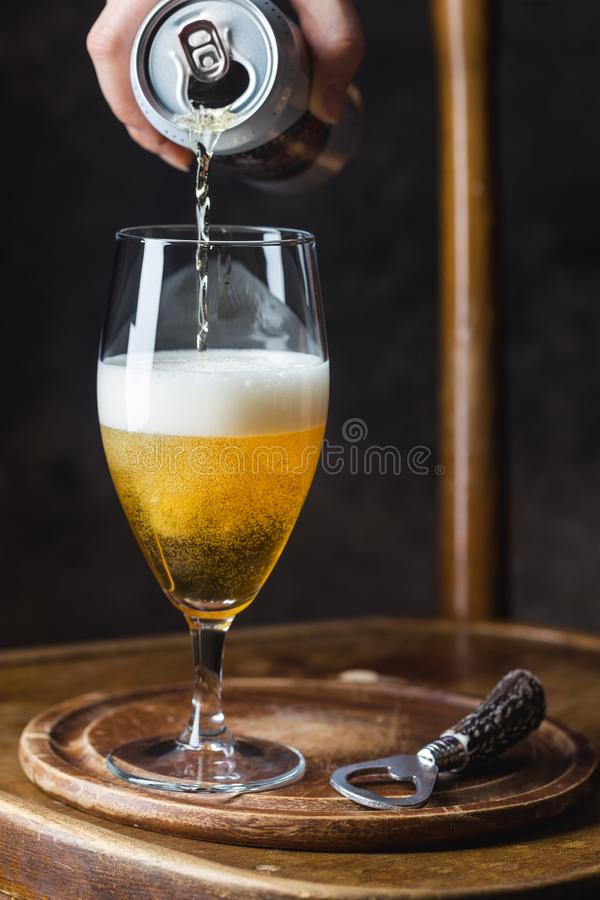 Beer pouring into glass. From a tin can on dark background royalty free stock photo