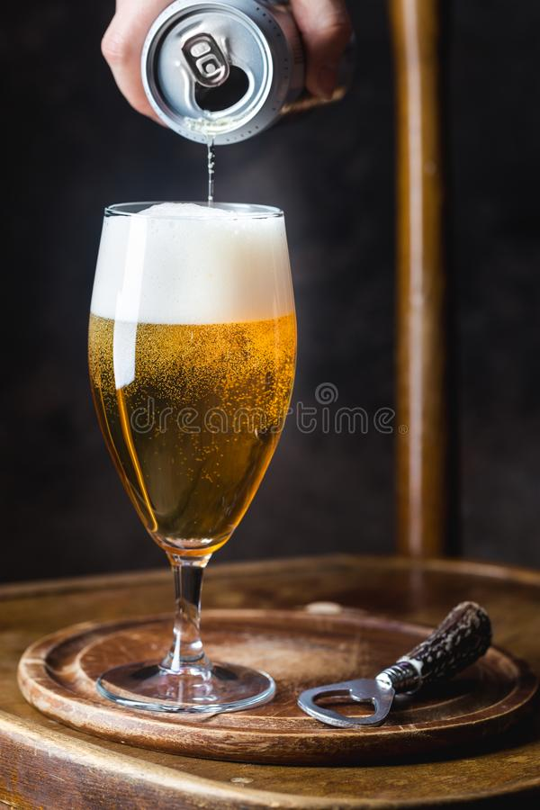 Beer pouring into glass. From a tin can on dark background stock photo