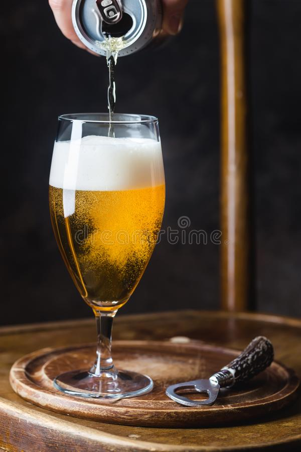 Beer pouring into glass. From a tin can on dark background stock images