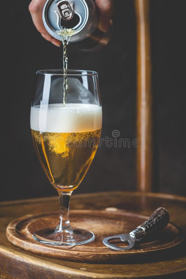 Beer pouring into glass. From a tin can on dark background stock image