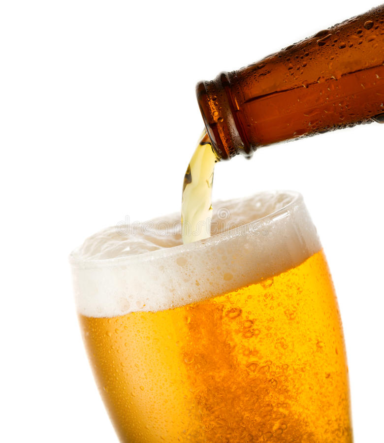 Beer is pouring into glass. On white background stock photo