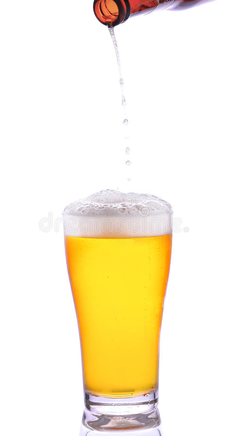 Beer is pouring into glass. On white background royalty free stock images