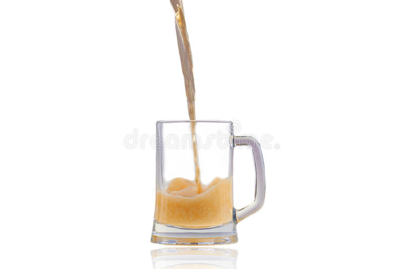 Beer pouring into half full glass over white background. With nice big foam and reflection of a glass royalty free stock photos