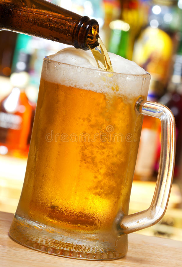 Beer pouring into mug. In a bar royalty free stock photos