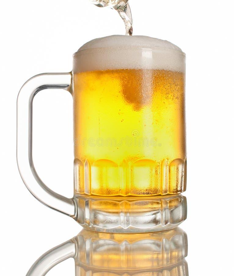 Beer pouring on mug royalty free stock image