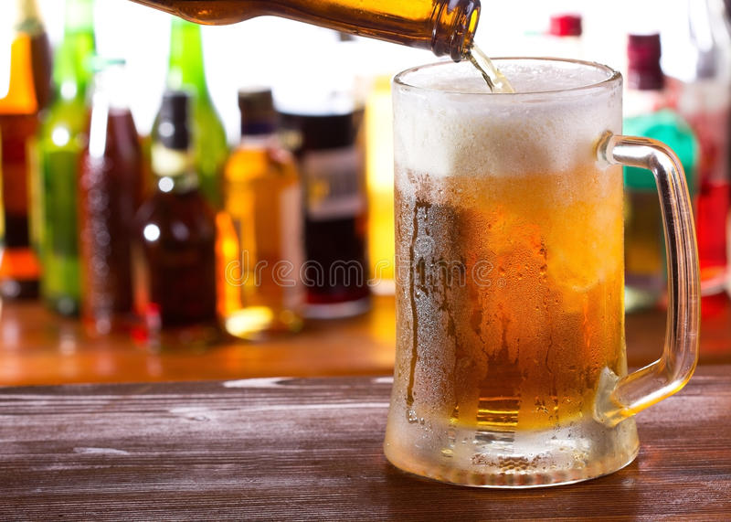 Beer pouring into mug. In a bar stock photography
