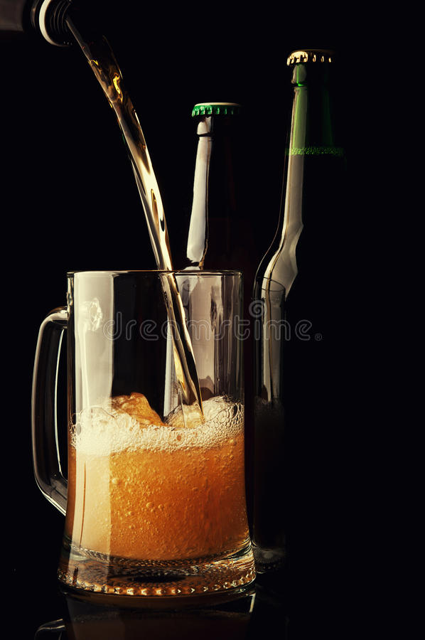 Beer pouring in mug. On black background royalty free stock photos