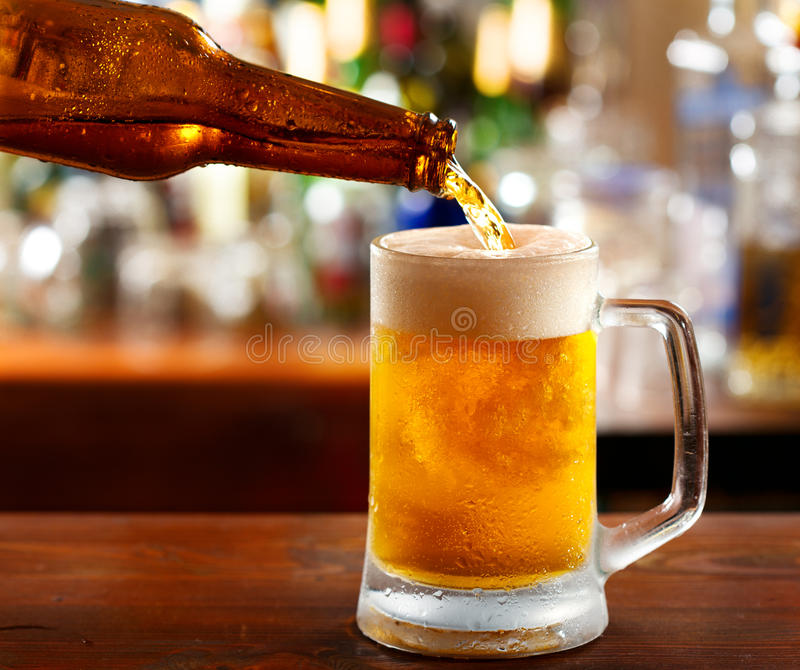 Beer pouring into mug. In a bar stock photo