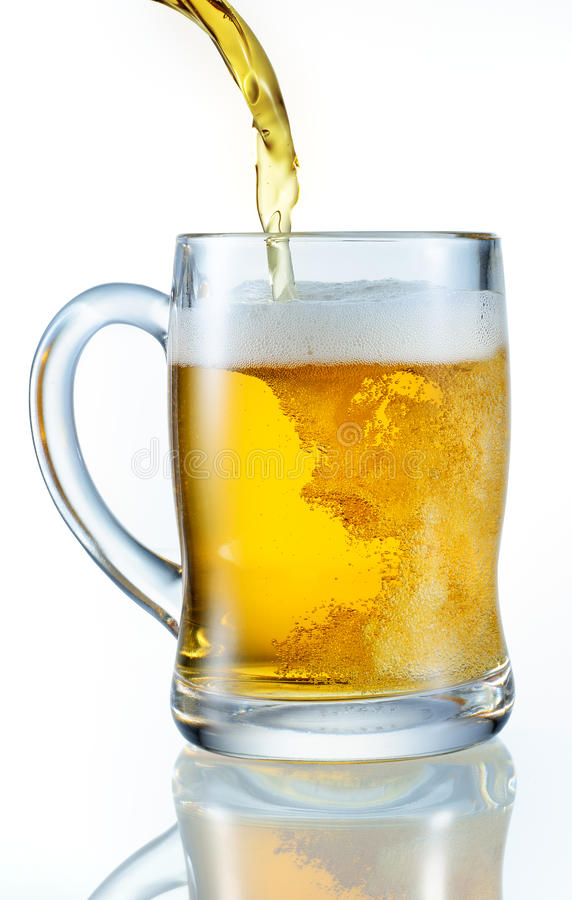Beer pouring into mug. Isolated on white background royalty free stock photo