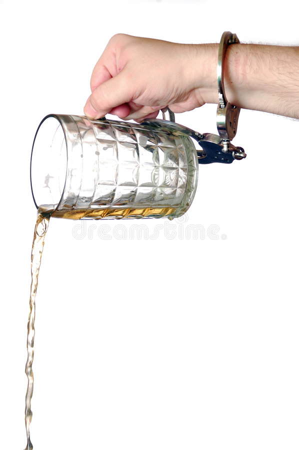 Beer pouring out. Of a mug by the hand chained to it with handcuffs royalty free stock photos