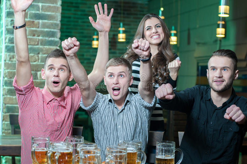 Beer Pub. Three men and one girl with beer rejoice the victory of their favorite team in the pub stock images