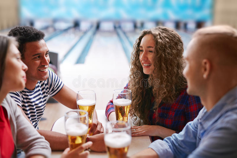 Beer relax. Happy young friends refreshing with beer after bowling stock photos