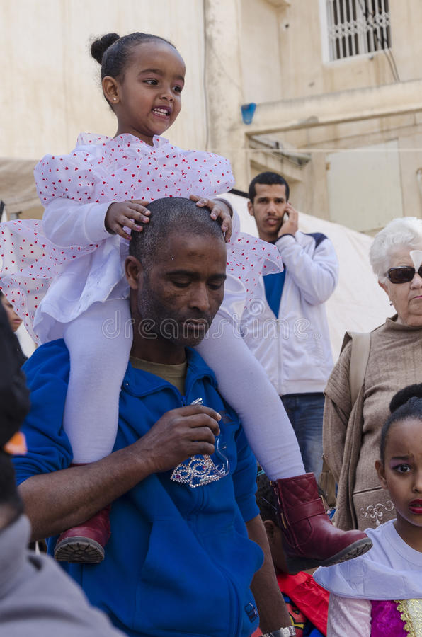 Beer-Sheva, ISRAEL - March 5, 2015: Afro-American father and daughter in a white dress on her shoulders. Purim in the city of Beer-Sheva on March 5, 2015 in royalty free stock image