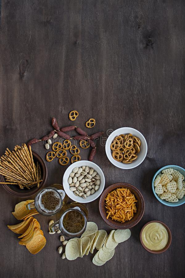 Beer snacks. Chips, nuts, pistachios for beer. Wood background. View from above. Place for text. Oktoberfest royalty free stock photo
