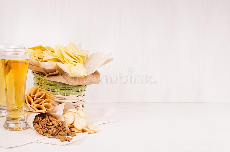 Beer snacks in craft paper and two lager beer in glass on soft fresh wooden table. stock photography